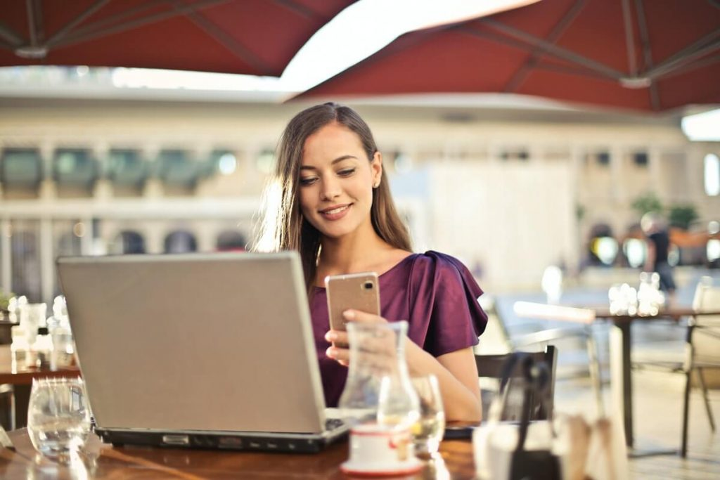 Cloud Computing on the Go - Woman accesses files on phone and laptop at a cafe